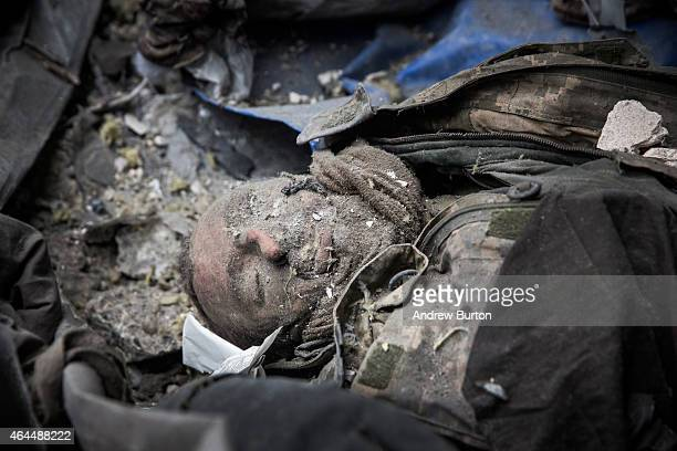 A dead Ukrainian soldier lies amongst the wreckage of the destroyed Donetsk airport after being recovered by Ukrainian soldier prisonersofwar who...