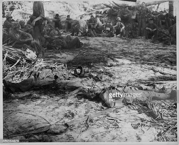 A dead US Marine and Japanese soldier lie together where they fell watched by other marines as they rest during the Pacific Campaign of World War Two...