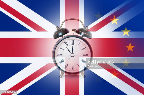 a brexit deadline concept. with an alarm clock over layered with the union jack and e.u flags. - brexit stock pictures, royalty-free photos & images