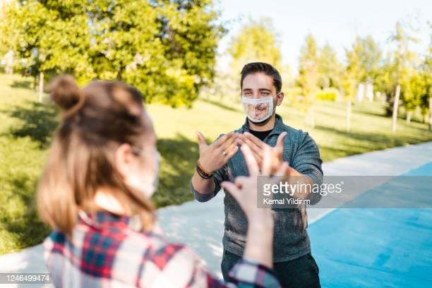 dove en slechthorende jonge volwassenen die speciaal gezichtsmasker voor lip-lezing dragen - gebaren stockfoto's en -beelden