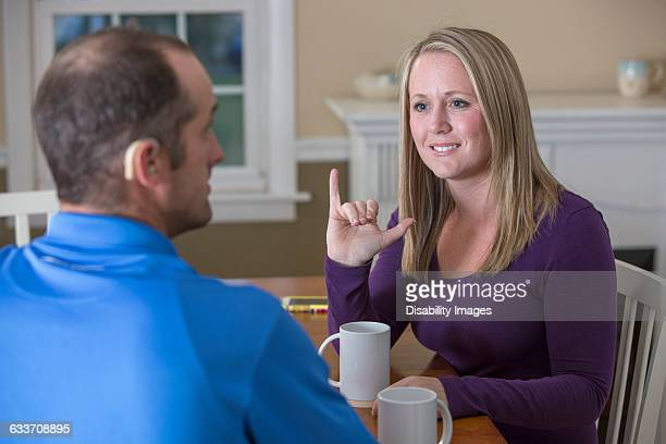Deaf Caucasian couple signing at dinner table