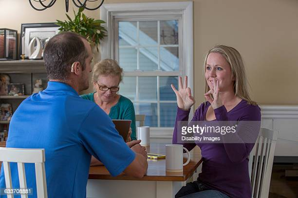 Deaf Caucasian friends signing at dinner table