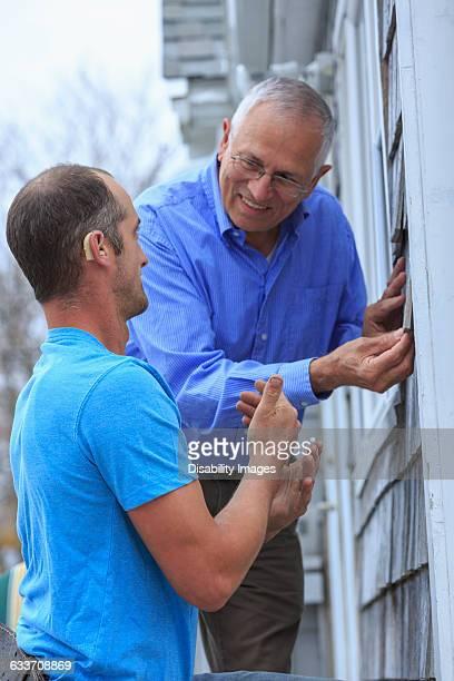 Deaf Caucasian homeowner signing to repairman