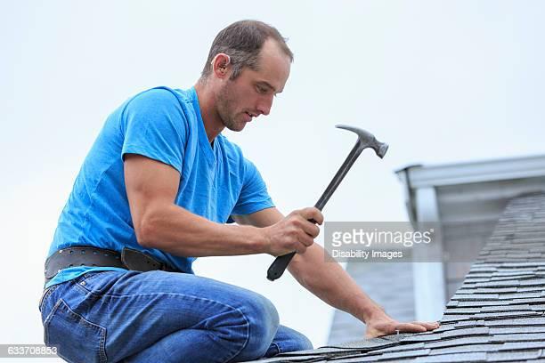 Deaf Caucasian roofer hammering on roof