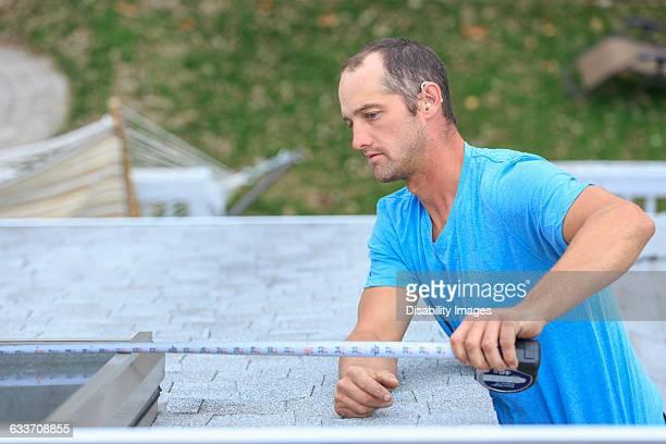 Deaf Caucasian roofer measuring skylight on roof