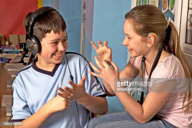 deaf children with hearing aids in a school class room using sign language - children only stock pictures, royalty-free photos & images