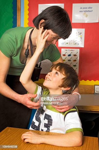 deaf children with hearing aids in a school class room using sign language - cochlear implant stock pictures, royalty-free photos & images