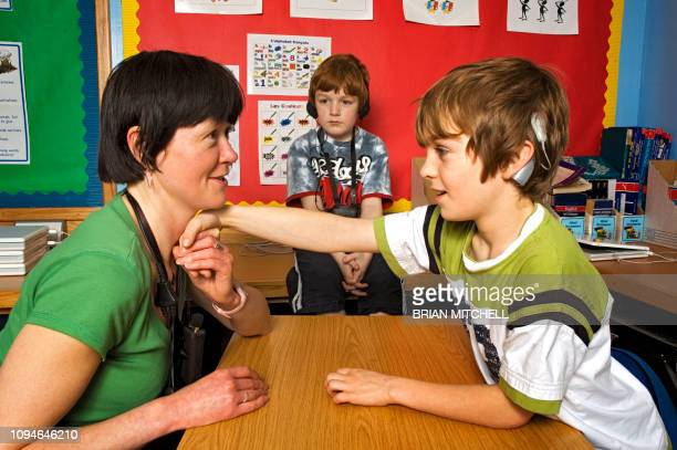 deaf children with hearing aids in a school class room using sign language - image stock-fotos und bilder