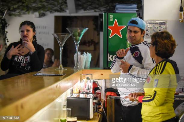 Deaf customers and the bartenders communicate through sign language at the 'Sin Palabras' coffee bar in Bogota on July 19 2017 With menus with...