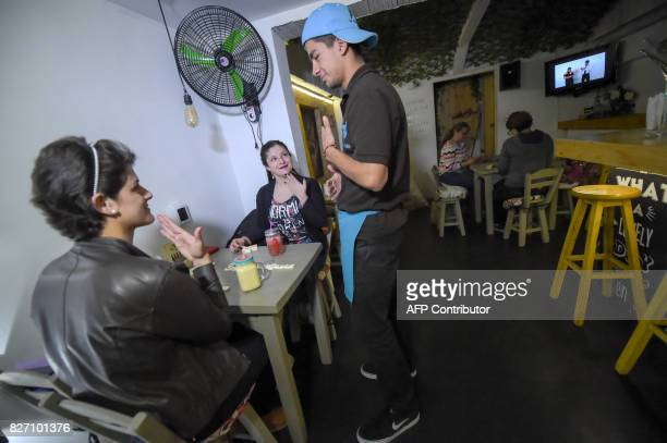 Deaf customers and the waiter communicate through sign language at the 'Sin Palabras' coffee bar in Bogota on July 19 2017 With menus with vignettes...