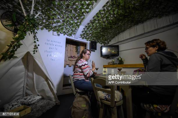 Deaf customers communicate through sign language at the 'Sin Palabras' coffee bar in Bogota on July 19 2017 With menus with vignettes depicting sign...
