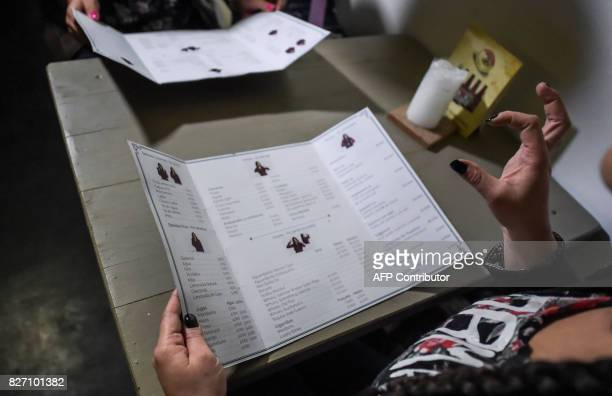 Deaf customers discuss the menu through sign language at the 'Sin Palabras' coffee bar in Bogota on July 19 2017 With menus with vignettes depicting...