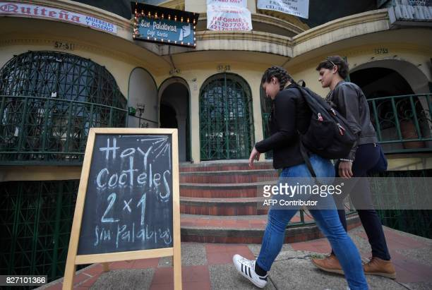 Deaf customers go to the 'Sin Palabras' coffee bar in Bogota on July 19 2017 With menus with vignettes depicting sign language lamps to call the...