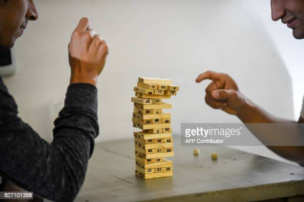Deaf customers play a game at the 'Sin Palabras' coffee bar in Bogota on July 19 2017 With menus with vignettes depicting sign language lamps to call...