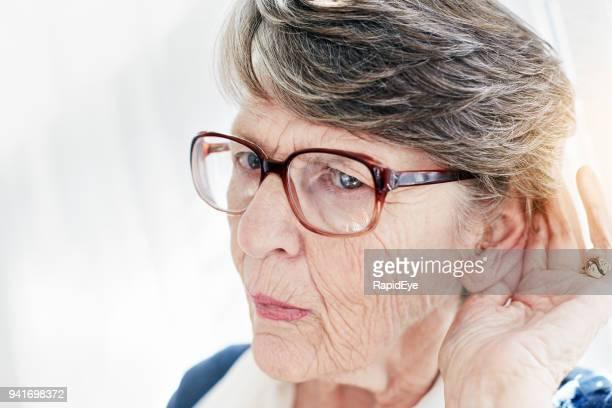 mulher velha surda olha de sobrancelhas franzidas, colocando a orelha e tentar ouvir - esforço - fotografias e filmes do acervo