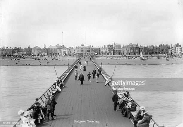 Deal Pier, Deal, Kent, 1890-1910. A view looking along the pier towards Deal with people sitting on benches in the foreground. The pier was designed...