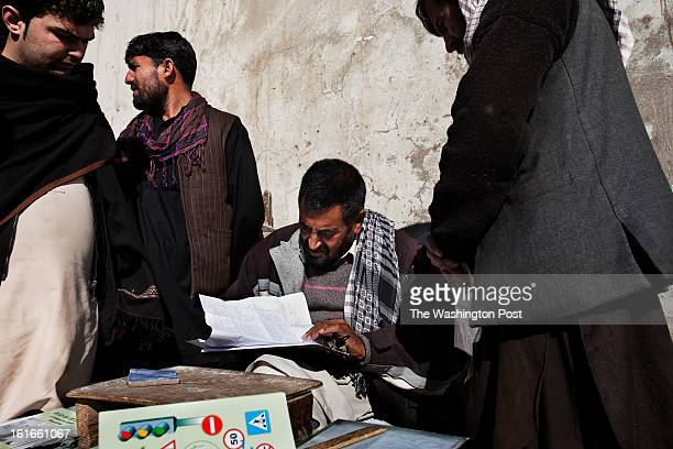 KABUL AFGHANISTAN – JANUARY A dealer helps his clients with their paperwork in his makeshift shop outside the traffic department in Kabul Obtaining a...
