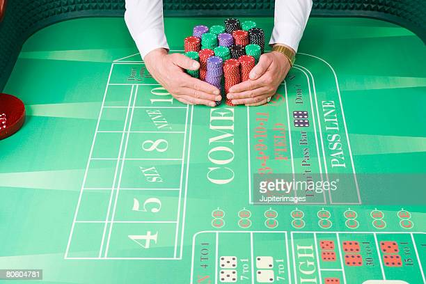 Dealer holding chips on gambling table