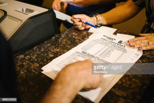 Dealer reviews a pick sheet with a guest before a bet is placed during the launch of full-scale sports betting at Dover Downs Hotel and Casino in...
