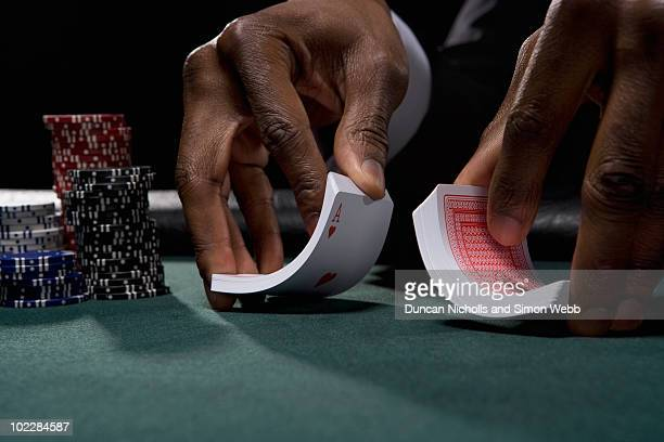 dealer shuffling cards in casino - shuffling stock photos and pictures