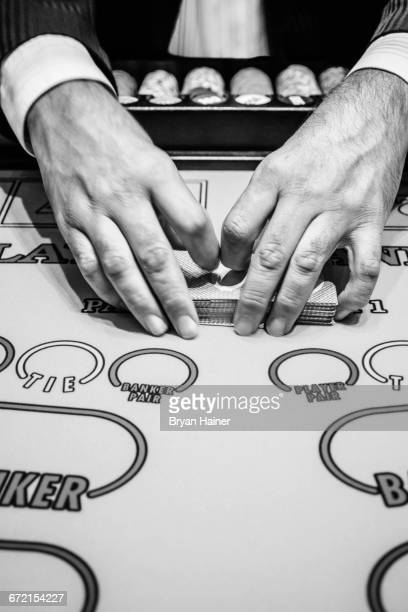 dealer shuffling playing cards at baccarat table - shuffling stock photos and pictures