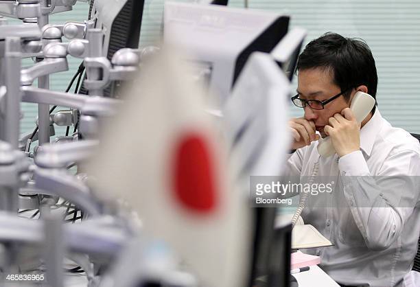 Dealer talks on a phone as a Japanese national flag sits on display at a foreign exchange brokerage in Tokyo, Japan, on Thursday, Jan. 30, 2014....