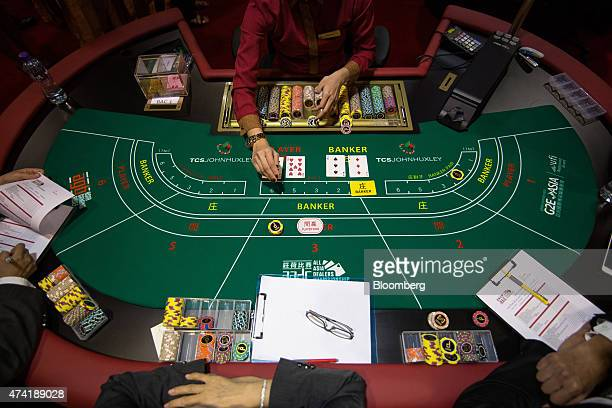 A dealer top handles gaming chips at a baccarat table during the All Asia Dealers' Championship at the Global Gaming Expo inside the Venetian Macau...