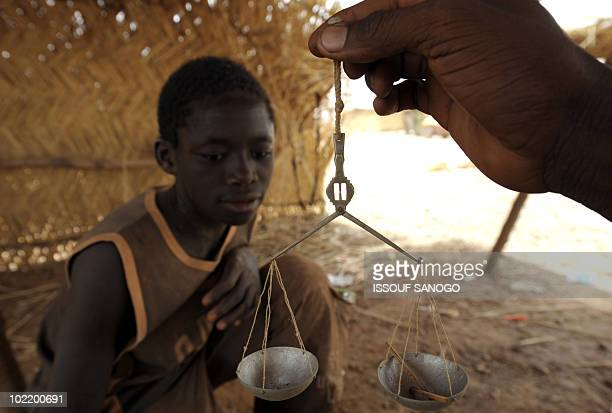 RETRAITE** A dealer weighs a young gold miner's find of the day in Namisgmathe largest gold washing site in the country some 200 kilometers from...
