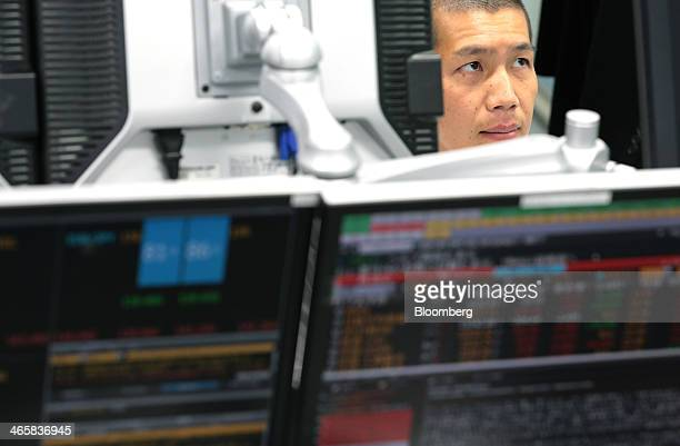 A dealer works at a foreign exchange brokerage in Tokyo Japan on Thursday Jan 30 2014 Japanese stocks fell with the Topix index closing at its lowest...