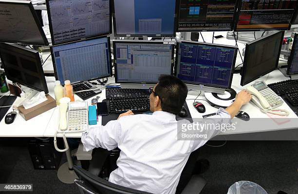 Dealer works at a foreign exchange brokerage in Tokyo, Japan, on Thursday, Jan. 30, 2014. Japanese stocks fell, with the Topix index closing at its...