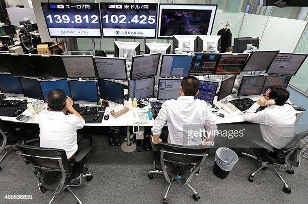 Dealers work at a foreign exchange brokerage in Tokyo Japan on Thursday Jan 30 2014 Japanese stocks fell with the Topix index closing at its lowest...