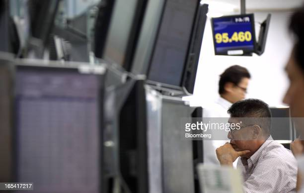 Dealers work in front of a monitor displaying the exchange rate of the yen against the US dollar at a foreign exchange brokerage in Tokyo Japan on...