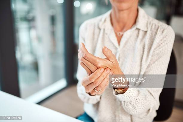 dealing with hand pain and stiffness - osteoporosis stock pictures, royalty-free photos & images