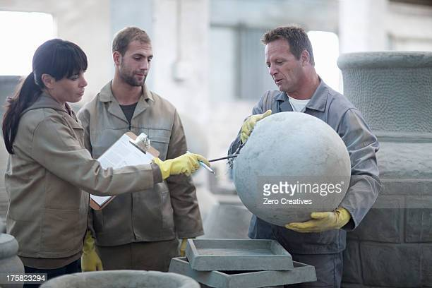 dealing with sales in pottery factory - men with huge balls stock photos and pictures