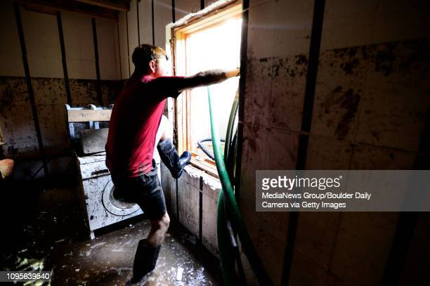 Dean Beacom crawls in and out of his basement window as he tries to pump water out of his flooded Boulder Colorado home Paul Aiken / The Daily Camera...