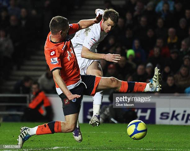 Dean Bowditch of MK Dons holds off Clint Hill of Queens Park Rangers to score during the FA Cup Third Round match between MK Dons and Queens Park...