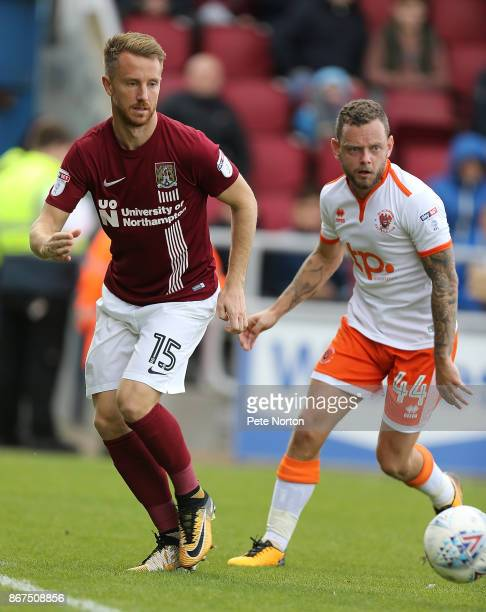 Dean Bowditch of Northampton Town plays the ball watched by Jay Spearing of Blackpool during the Sky Bet League One match between Northampton Town...