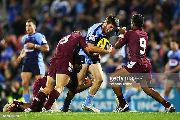 Dean Britt of the NSW is tackled by Brenko Lee and Kierran Moseley of QLD during the U20's State of Origin match between the New South Wales Blues...