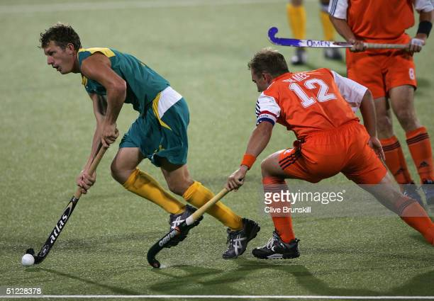 Dean Butler of Australia dribbles against the defense of Jeroen Delmee of the Netherlands during the men's field hockey gold medal match on August 27...