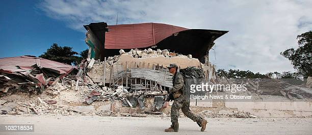 Dean Cobian, a soldier with Charlie Company 1/325th, walks past a collapsed building one block from the Presidential Palace in Port-au-Prince, Haiti,...