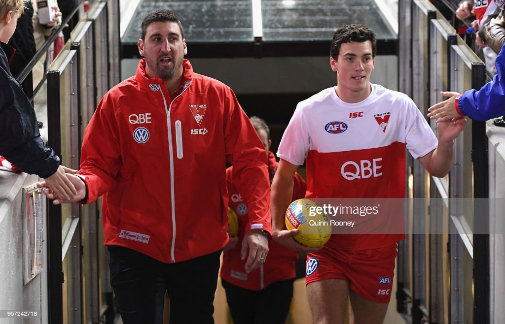 Dean Cox the assistant coach and Tom McCartin of the Swans walk out onto the field during the round eight AFL match between the Hawthorn Hawks and the Sydney Swans at Melbourne Cricket Ground on May 11, 2018 in Melbourne, Australia.