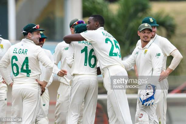 Dean Elgar , Kagiso Rabada and Quinton de Kock of South Africa Nkrumah Bonner of West Indies during day 1 of the 1st Test between South Africa and...