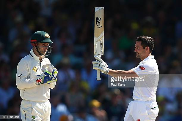 Dean Elgar of South Africa celebrates his century as Peter Nevill of Australia looks on during day three of the First Test match between Australia...