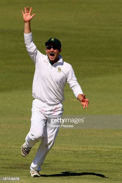 Dean Elgar of South Africa celebrates the wicket of Michael Hussey of Australia off the bowling of Dale Steyn of South Africa during day four of the...