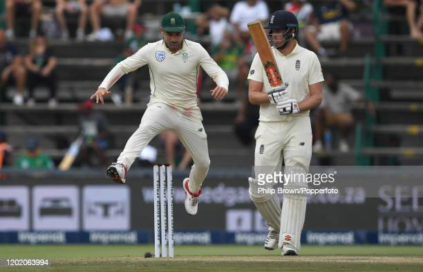 Dean Elgar of South Africa leaps the stumps as Dom Sibley looks on during Day Three of the Fourth Test at the Wanderers between England and South...