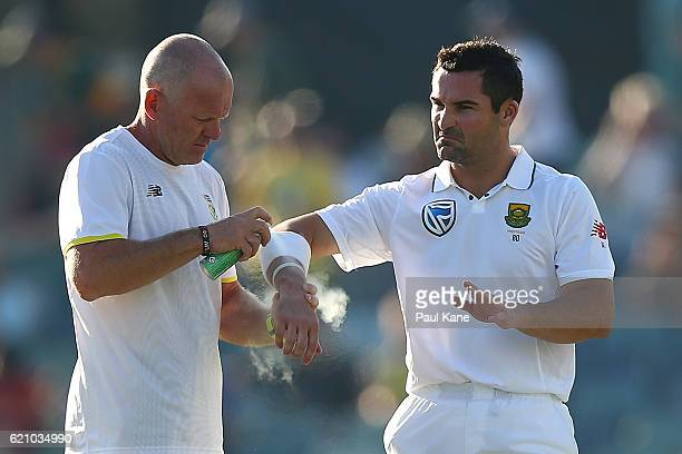 Dean Elgar of South Africa receives treatment to his right wrist after being struck by a delivery during day two of the First Test match between...