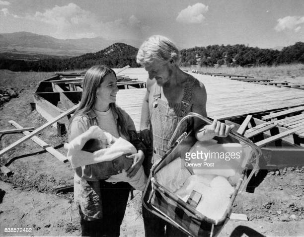 Dean Fleming casts admiring look at his 3weekold daughter Lea in the arms of his wife Linda They're standing beside circularshaped foundation of...