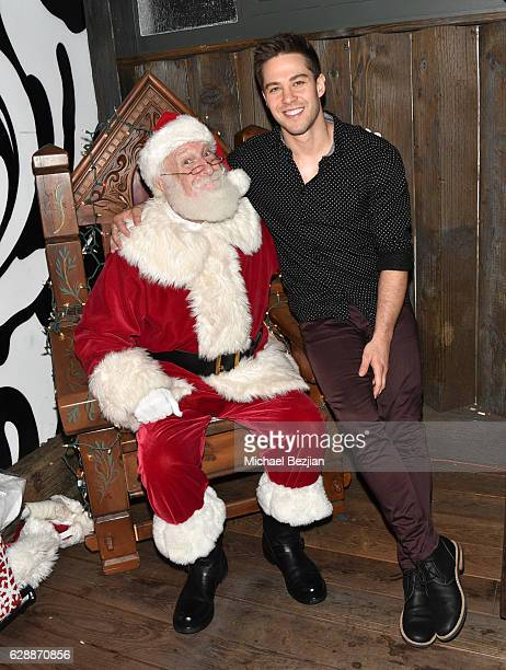 Dean Geyer and Santa at Not For Sale x Z Shoes Benefit at Estrella Sunset on December 9, 2016 in West Hollywood, California.