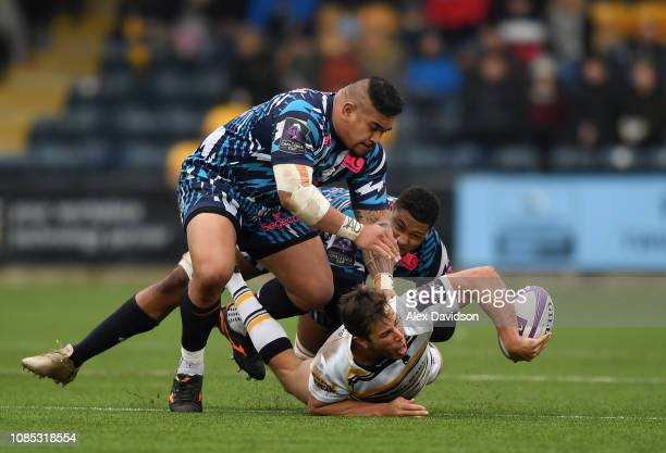 Dean Hammond of Worcester Warriors attempts to offload the ball as he is tackled by Ryan Chapuis of Stade Francais Paris and Elias El Ansari of Stade...