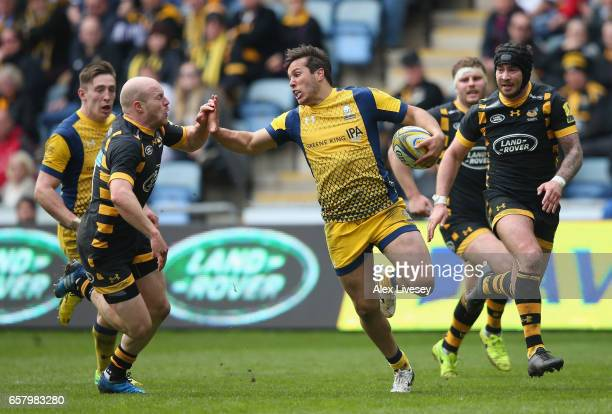 Dean Hammond of Worcester Warriors holds off a challenge from Joe Simpson and Danny Cipriani of Wasps during the Aviva Premiership match between...
